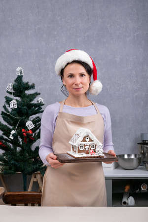 Woman chef in Santa hat holds gingerbread house in her hands. Christmas mood. Stok Fotoğraf