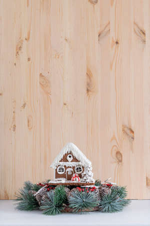 Gingerbread house and Christmas wreath on light wooden background. Copy space.