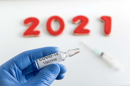 Doctors hand holds an ampoule with COVID-19 vaccine against inscription 2021 background.