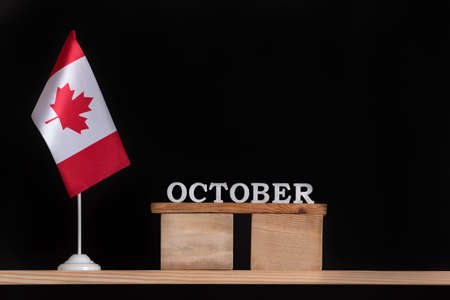 Wooden calendar of October with Canadian flag on black background. Autumn holidays in Canada.