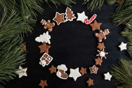 Ginger bread cookies in circle form on black background and spruce branches. Copy space