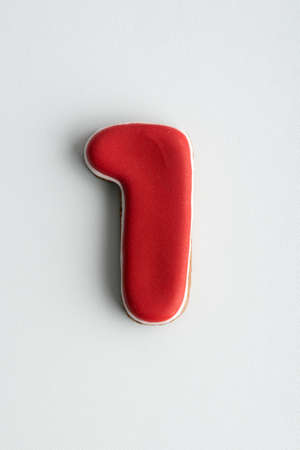 Glazed painted cookies number 1. Gingerbread cookies as numbers on white background.