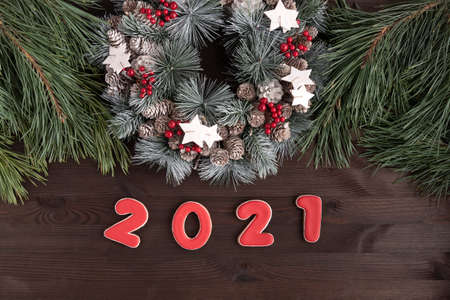 Christmas wreath and the inscription in 2021 of gingerbread on wooden background. New Year concept.