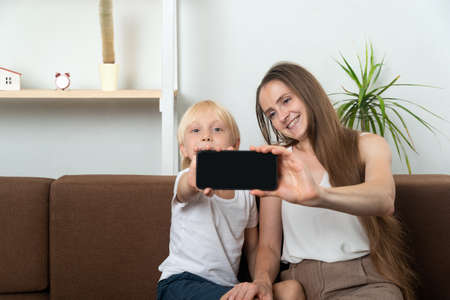 Young mom takes selfie with her son. Mom and child show screen of smartphone.