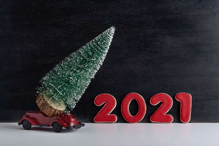 Toy car carries small Christmas tree against the background of inscription 2021. New Year is coming. Stok Fotoğraf
