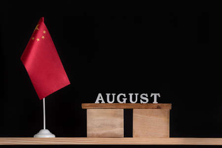 Wooden calendar of August with Chinese flag on black background. Holidays of China in August