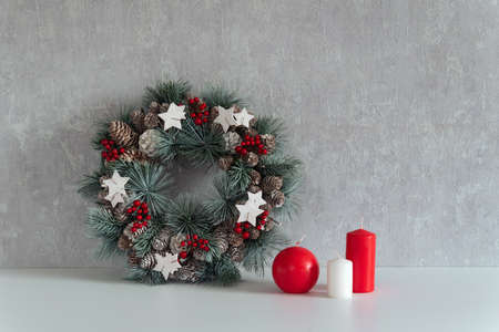 Christmas decorations: christmas wreath and candles on gray background. Cozy interior
