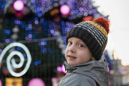 Portrait of boy in hat against the Christmas tree background. Preparing for Christmas.