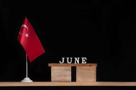Wooden calendar of June with Turkish flag on black background. Holidays of Turkey in June