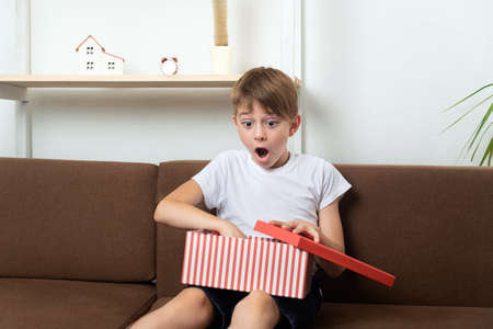 Surprised happy boy opened gift. Child with gift box with an open box in his hands. Stok Fotoğraf