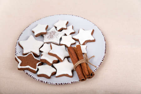 Glazed gingerbread stars and cinnamon sticks on plate. Christmas cookies.