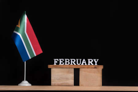 Wooden calendar of February with RSA flag on black background. Dates of South Africa in February Stok Fotoğraf