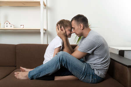Father and son leaning foreheads. Relationship between father and son. Close bond between father and child. Standard-Bild