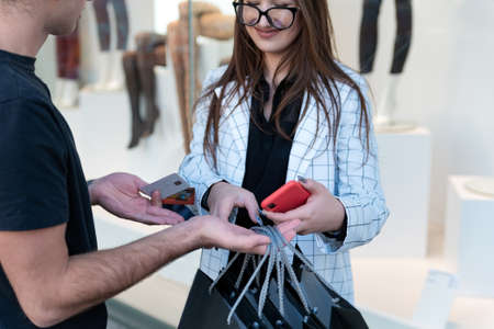 Young couple makes purchases in the mall. Shopping on Black Friday. Credit cards and smartphone in hands. Stok Fotoğraf