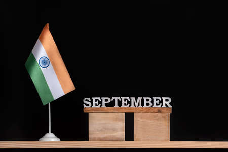Wooden calendar of September with Indian flag on black background. Holidays of India in September