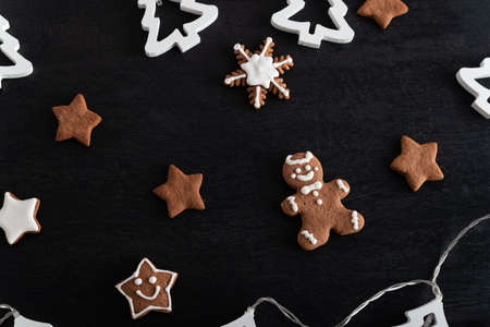 Christmas gingerbread man and stars on black background. Holiday baking.