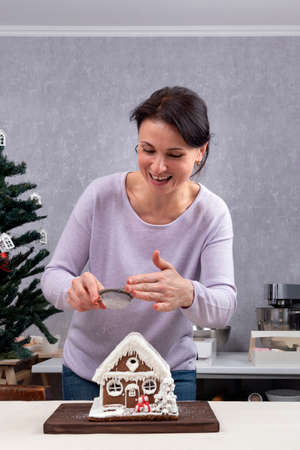 Beautiful woman sprinkles with powder gingerbread house. Christmas decorations. Stok Fotoğraf
