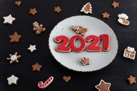Variety of Christmas cookies on the table. Number 2021 on a plate. Christmas baking.