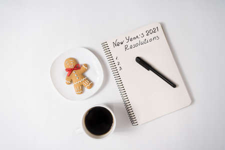 Phrase New Year's Resolutions 2021 in the notebook and pen. Gingerbread man and cup of coffee.