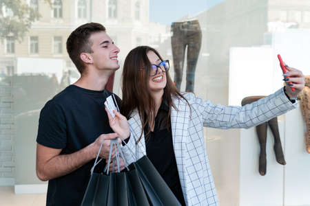 Portrait of happy young couple in shopping center on shopfront background. Selfie with credit cards and shopping bags. Zdjęcie Seryjne