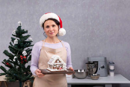 Woman chef in Santa hat holds gingerbread house in her hands. Christmas decoration in the kitchen.