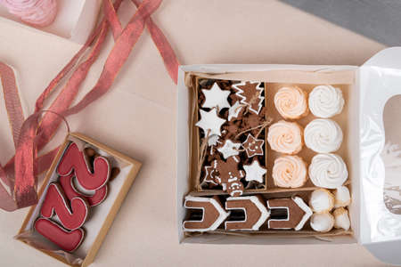New Years sweets in gift wrapping. Tasty glazed painted cookies and marshmallow