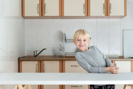 Blond boy stands in kitchen and smiles. Portrait of blond child in the kitchen.
