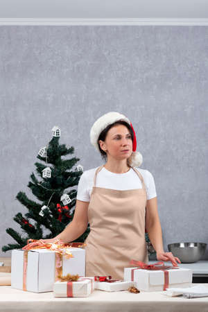 Woman in an apron and New Years hat next to gift boxes on New Year tree background. Vertical frame. Banco de Imagens