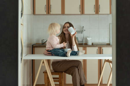 Mother and daughter in kitchen. Happy young mom and toddler have breakfast at home
