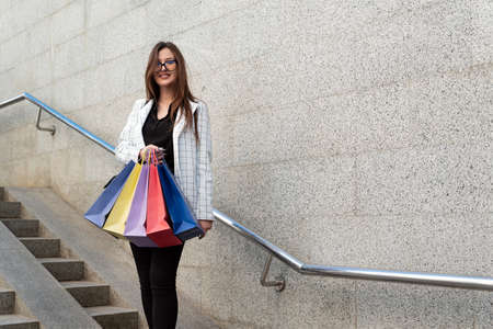 Portrait of cheerful young girl with multicolored shopping bags. Tourist with souvenirs.