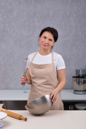 Portrait of woman in kitchen in kitchen apron. Vertical frame.