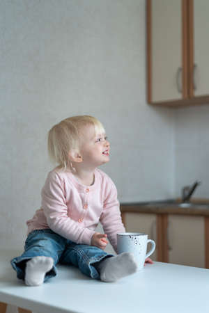 Smiling blond child in the kitchen with cup in hands. Portrait of toddler in the kitchen. Banco de Imagens
