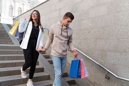 Young couple descending stairs with numerous packages after shopping.