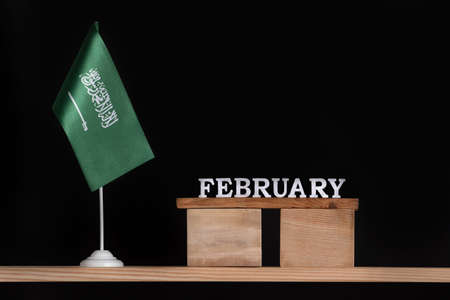 Wooden calendar of February with Saudi Arabia flag on black background. Dates of Saudi Arabia in February. Banco de Imagens