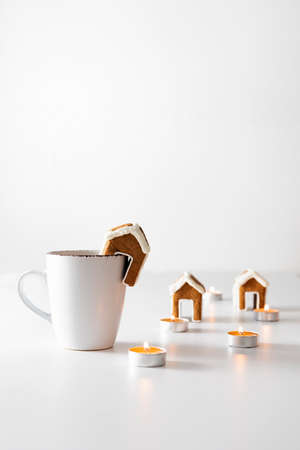 Cup of tea with gingerbread house and candles on white background. New years mood. Vertical frame.