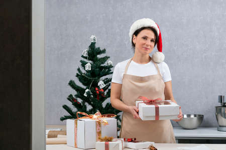 Confectioner woman in New Year's hat presents gift box in her hands against New Year tree background.