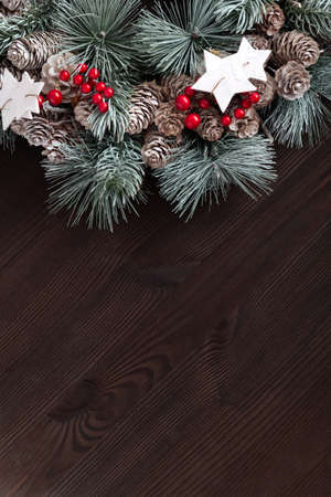 Christmas wreath on dark wooden background. New Year pattern. Copy space. Vertical frame.