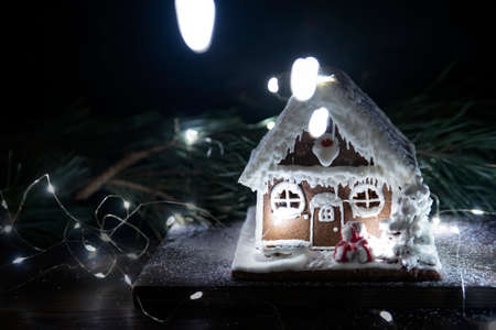 Gingerbread house surrounded by glowing garlands. New Years composition. New year.