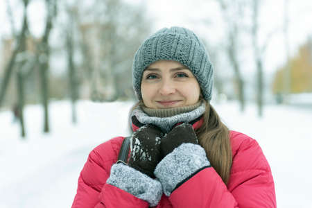 Portrait of young woman in hat on snow-covered park background