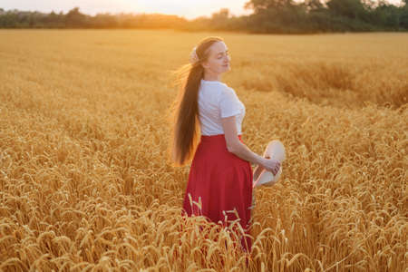 Young woman walks through field of ripe wheat at sunset. Natural beauty.