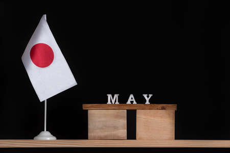 Wooden calendar of May with table Japanese flag on black background. Holidays of Japan in May.