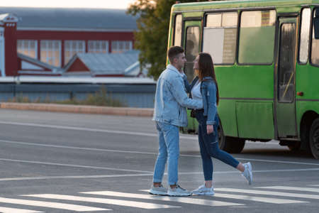 Guy escorts girl to bus, hugs and kisses. Couple in love saying goodbye at the bus stop. Banco de Imagens