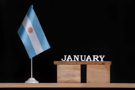 Wooden calendar of January with Argentine flag on black background. Holidays of Argentina in January.