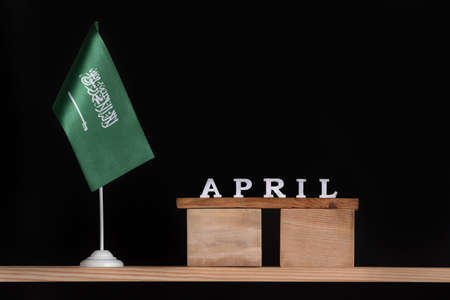 Wooden calendar of April with Saudi Arabia flag on black background. Dates of Saudi Arabia in April. Banco de Imagens