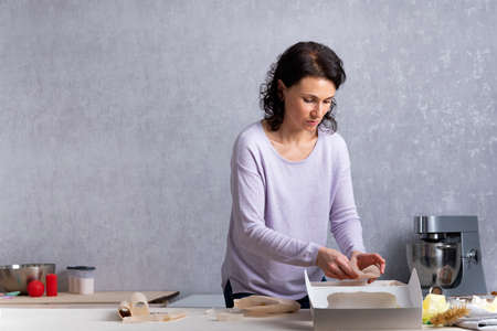 Young woman in kitchen is packing pastries in white cardboard box. Process of wrapping.