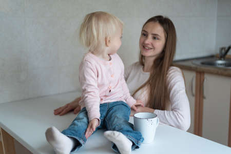 Young mother and cute little girl look at each other. Morning on kitchen.