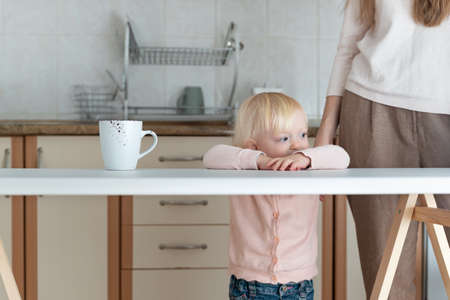 Young mom and baby in the kitchen. Mother and baby morning Banco de Imagens