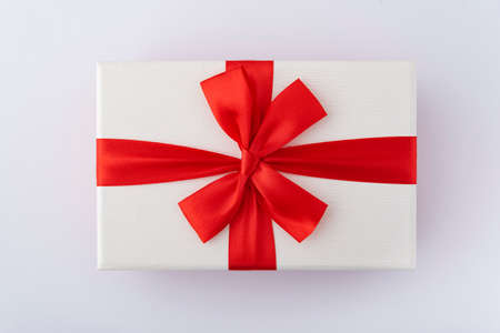 White box with red ribbon and bow on white background. Top view