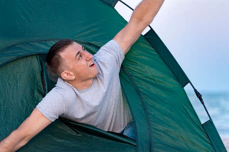 Man looks out of the tent and stretching. Morning in nature
