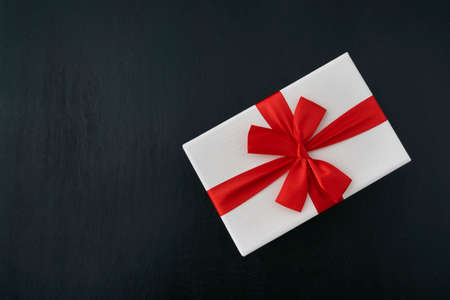 White gift box with red ribbon on black background. Top view. Gift wrapping Banco de Imagens